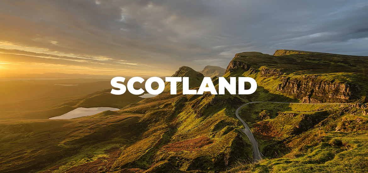 'Scotland' in white text over rugged green mountains at sunset