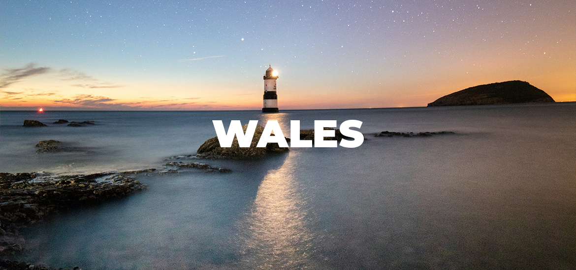 'Wales' in white text over nighttime image of a lighthouse at sea