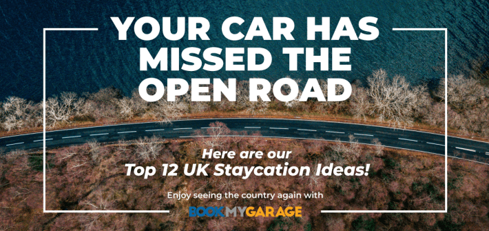 your car has missed the open road, here are our top 12 staycation ideas, enjoy seeing the country again with BookMyGarage in white text over aerial view of road driving along oceanside with trees either side