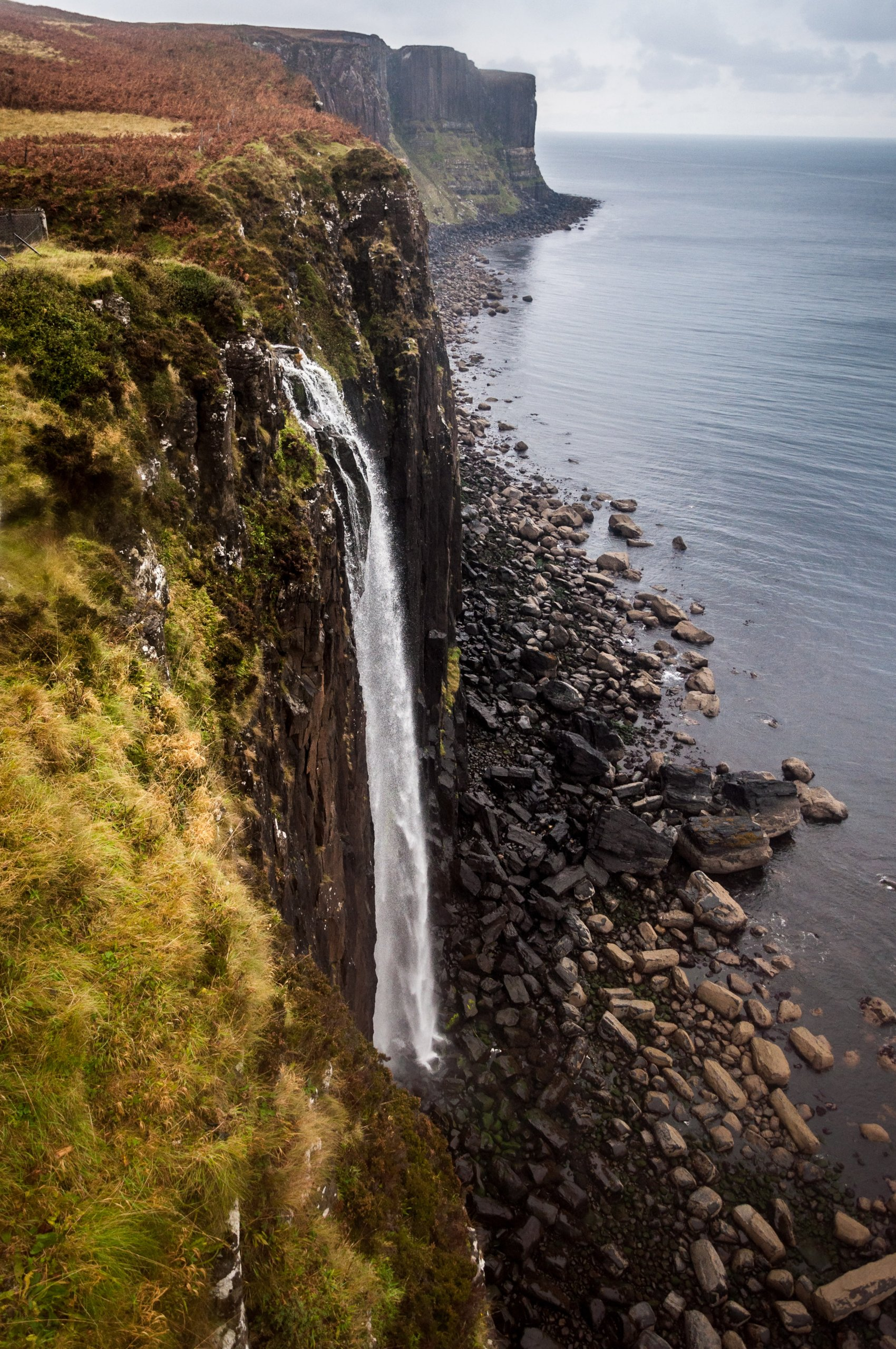 Portrait image of waterfall tumbling down cliff and meeting sea at the bottom