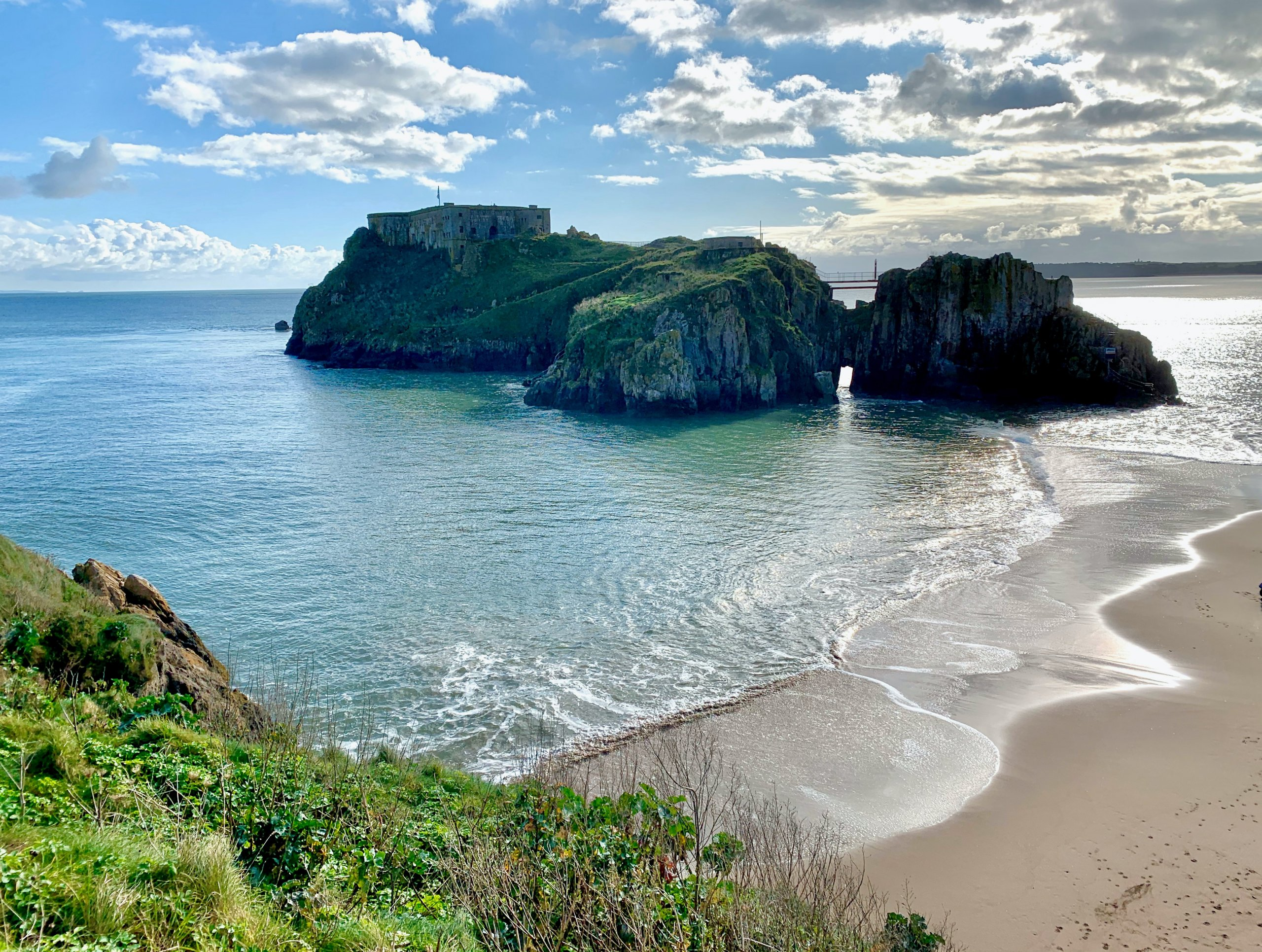 Sandy beach and calm ocean with three islands in ocean and fort atop the left most island at Tenby in Pembrokeshire