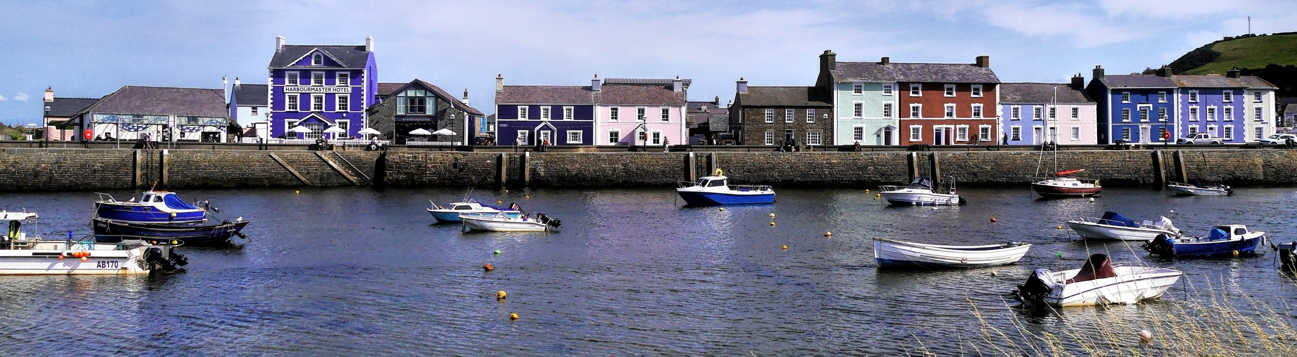 Purple, burgundy, cream, light green and brown painted houses on harbour side in Aberaeron, Wales, UK