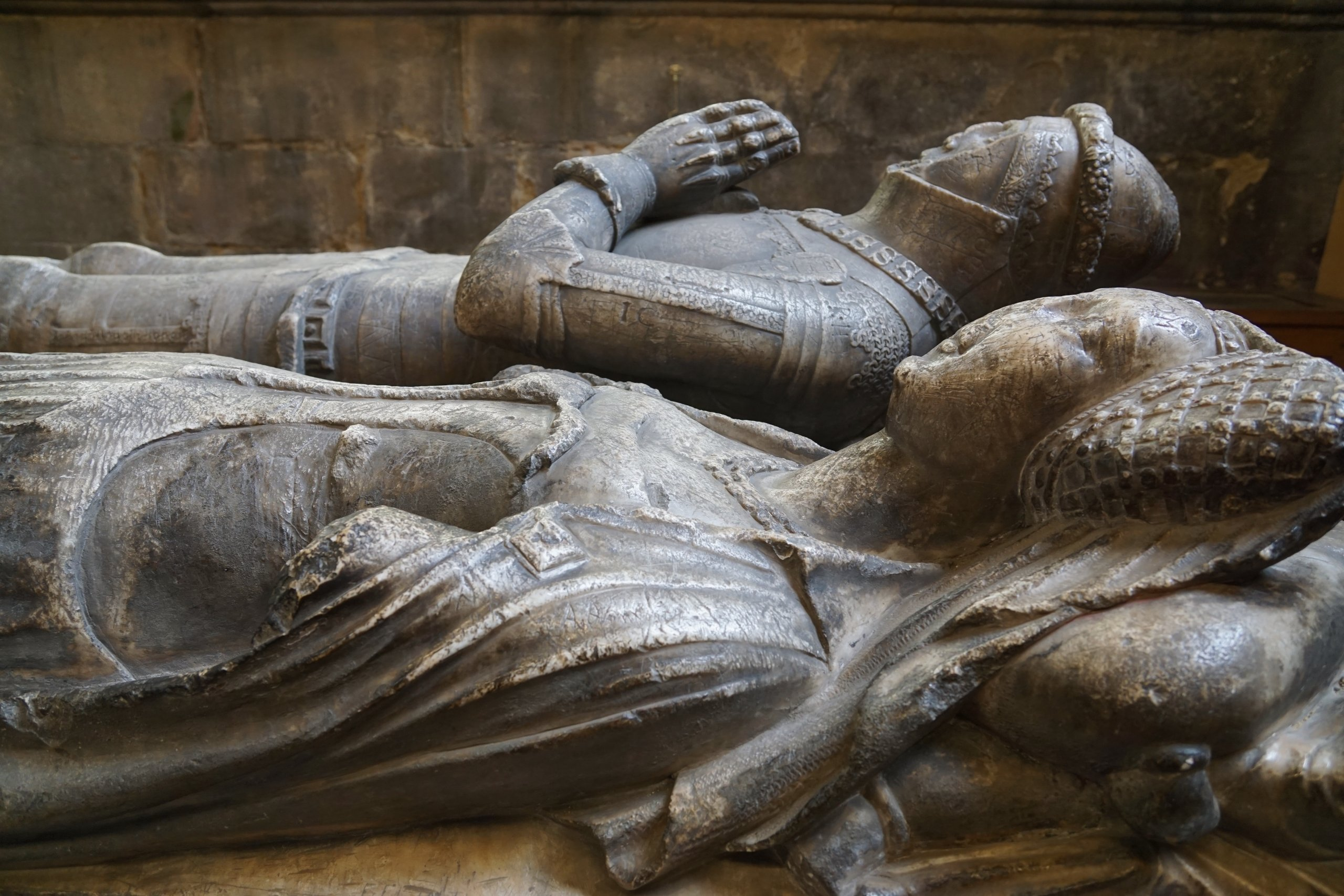 Bronze busts of sleeping man and woman, Medieval style burial inside church