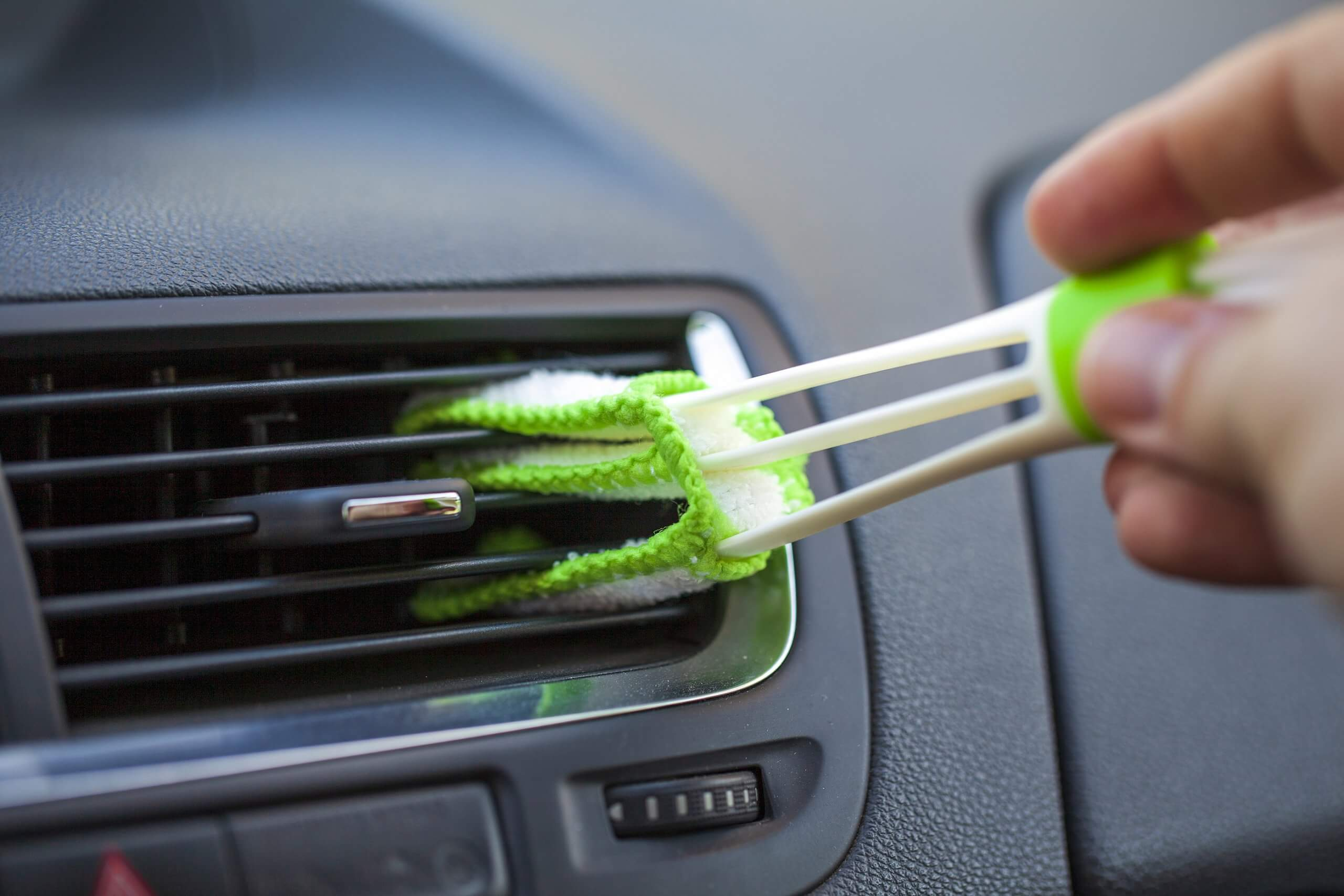 driver cleaning dust from their air conditioning vent with green brush