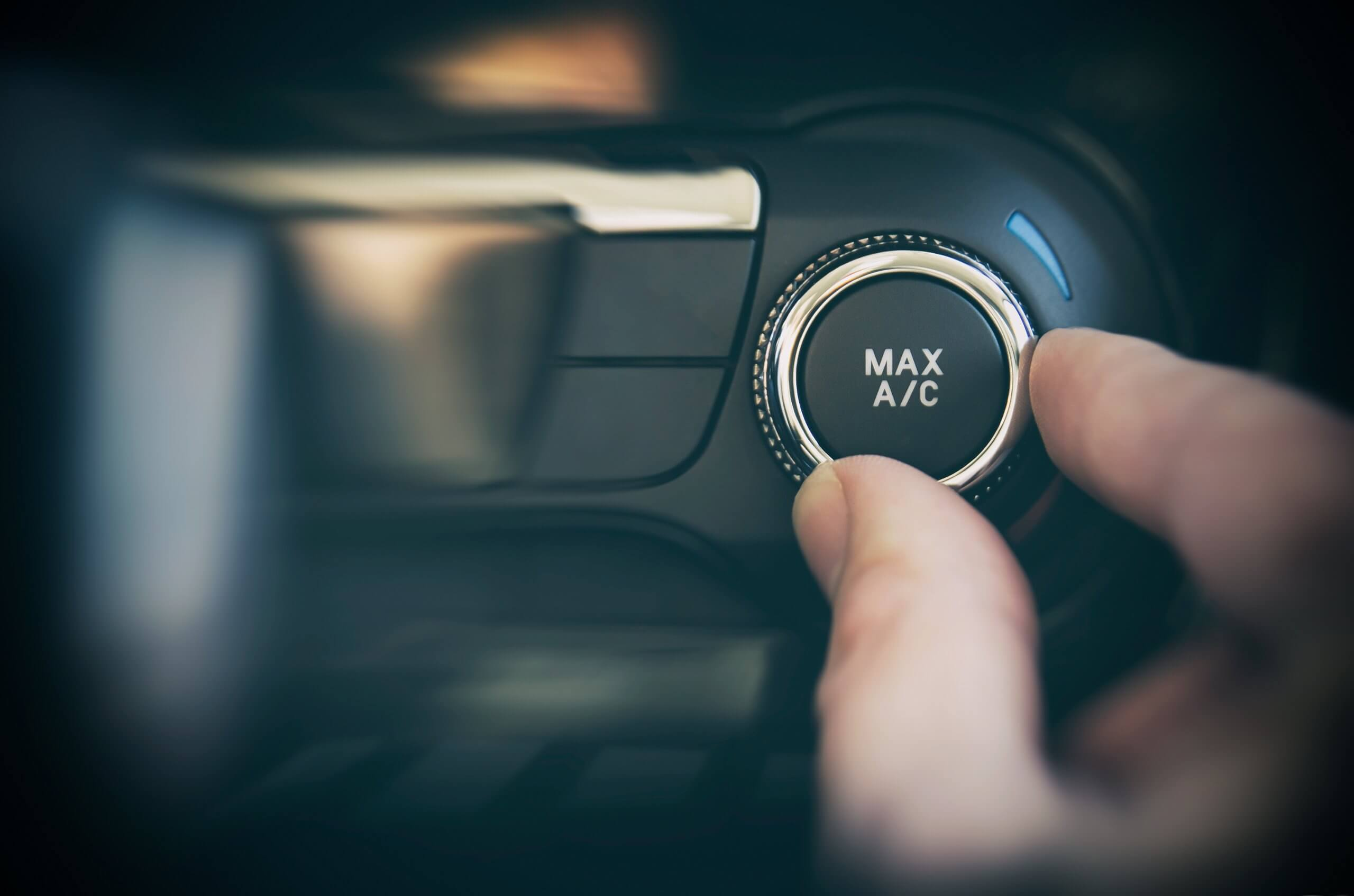 close up of driver turning air conditioning dial to cool the car cabin