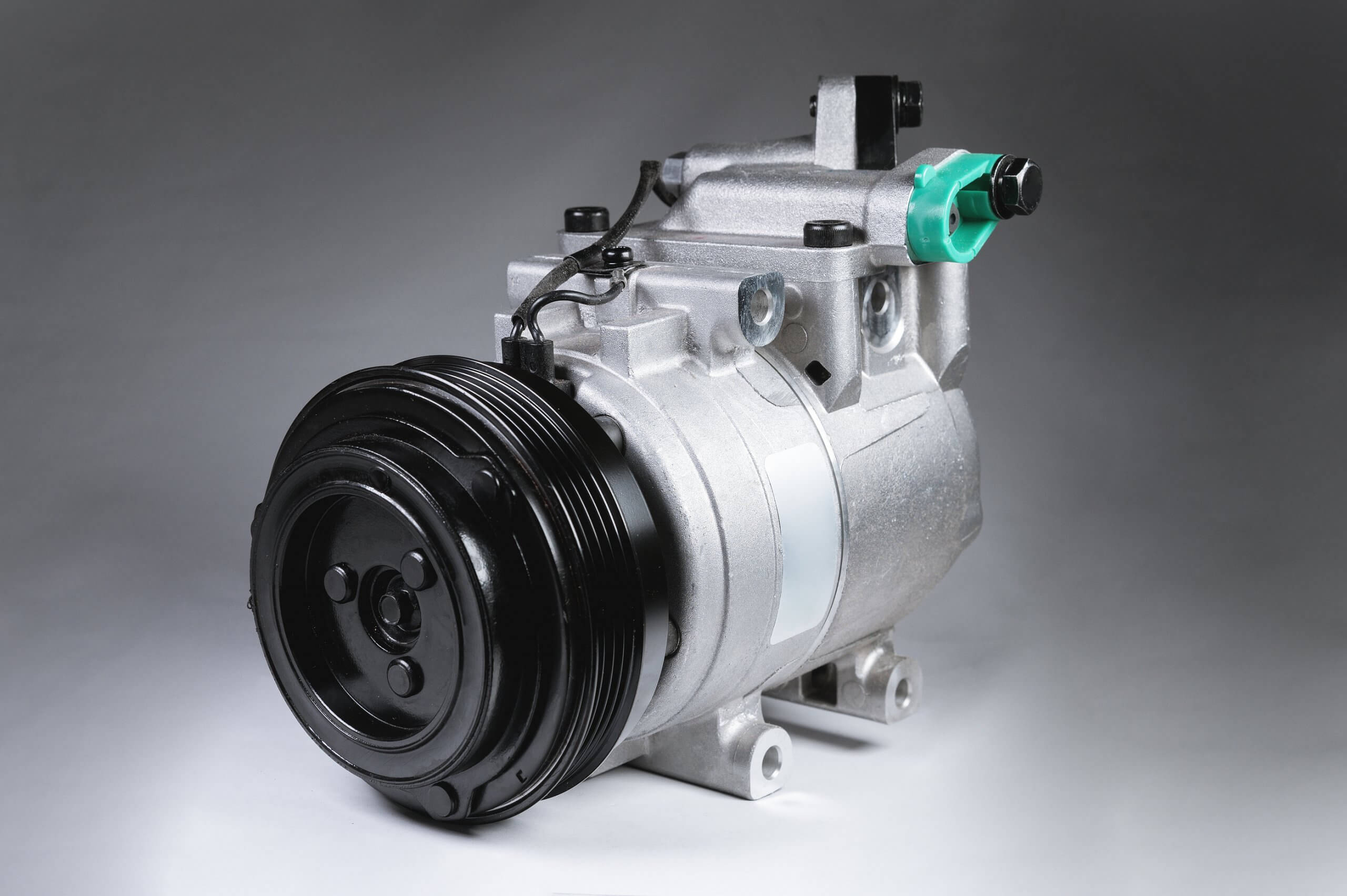 close up of a car air conditioning compressor on grey background