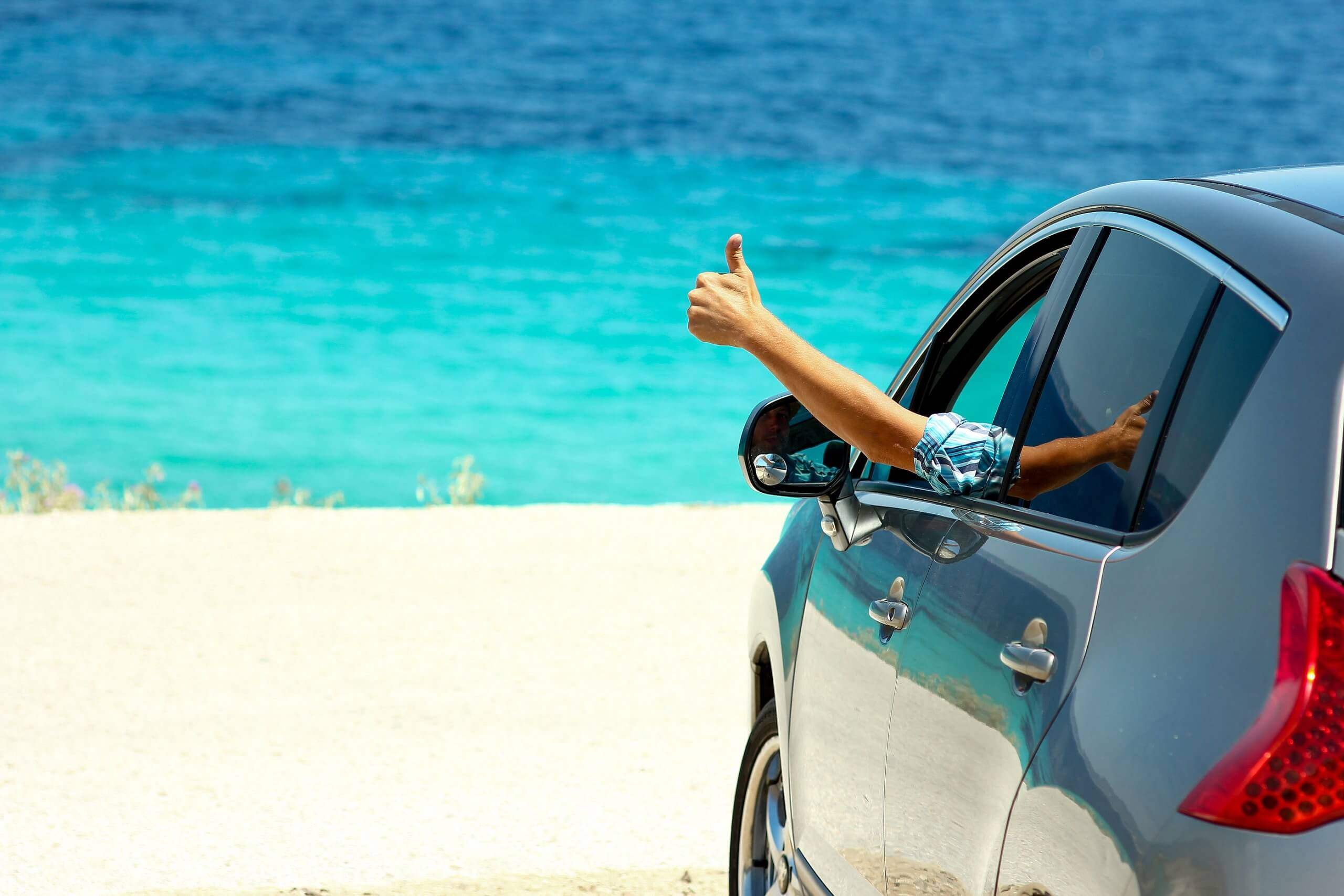 happy driver with thumb out the window of grey car on sandy beach with blue sea in background