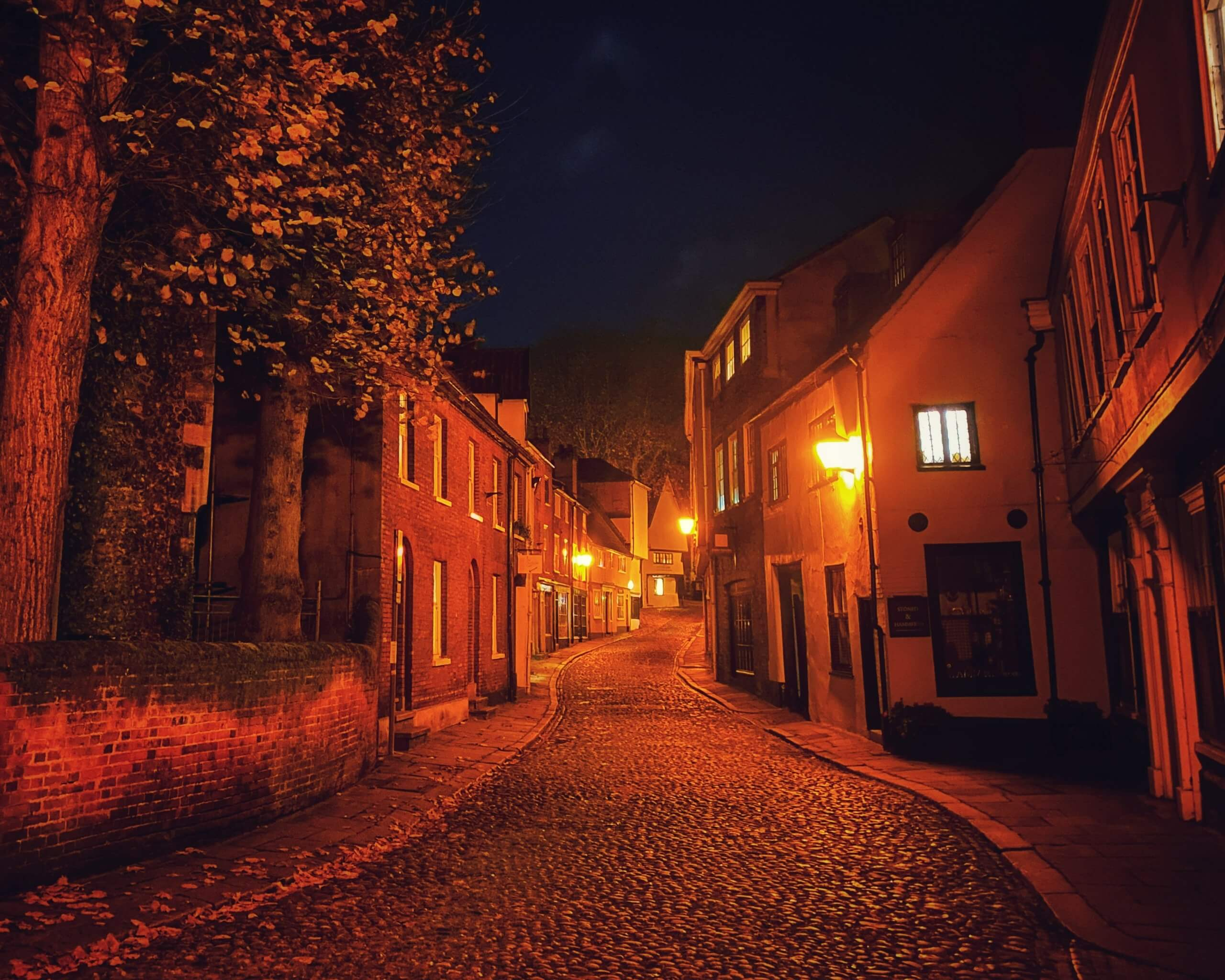 Cobbled street in Norwich, Norfolk, UK at night with red street lamps lighting the houses eerily
