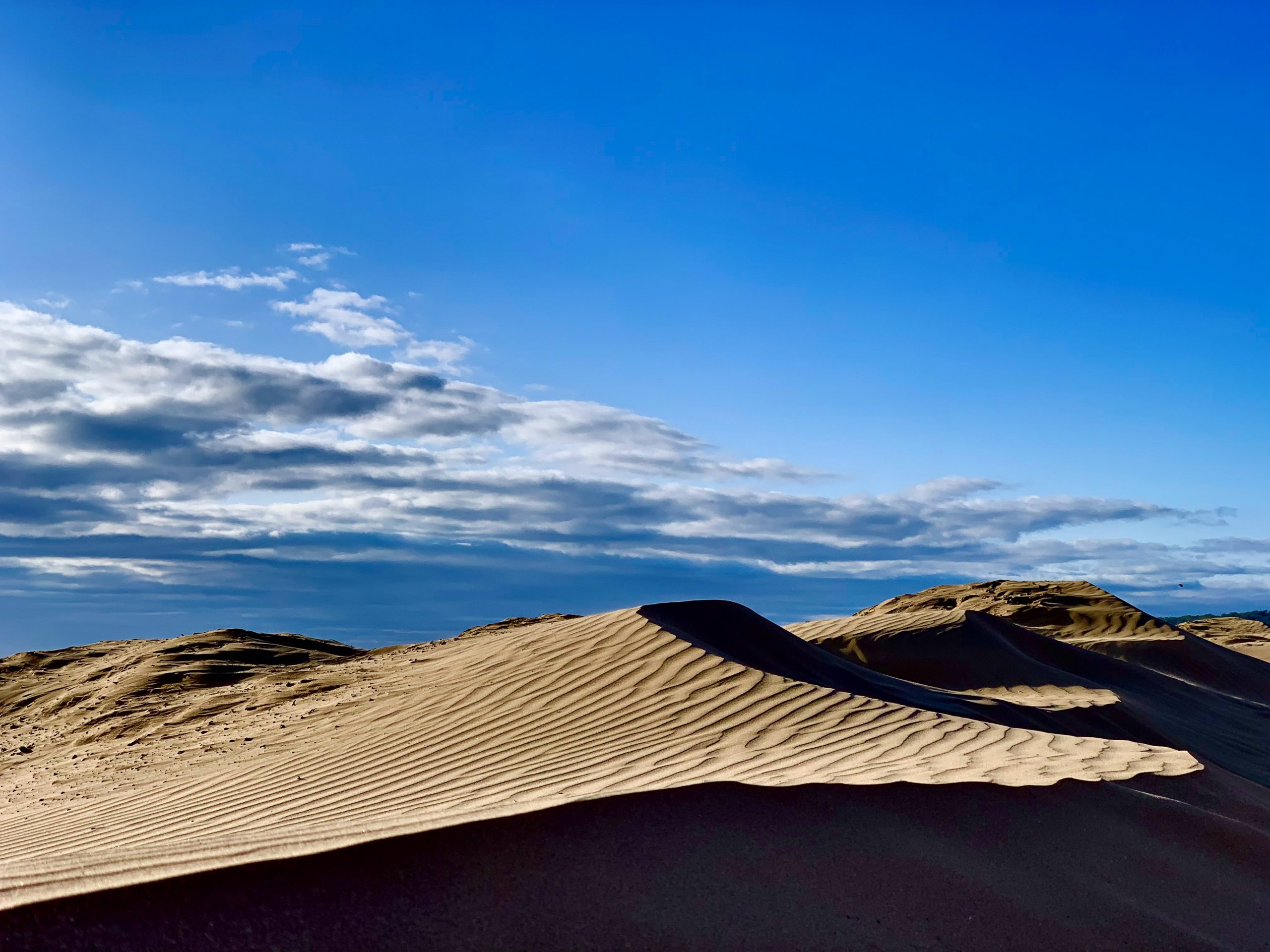 large sand dunes with sea in background and blue sky