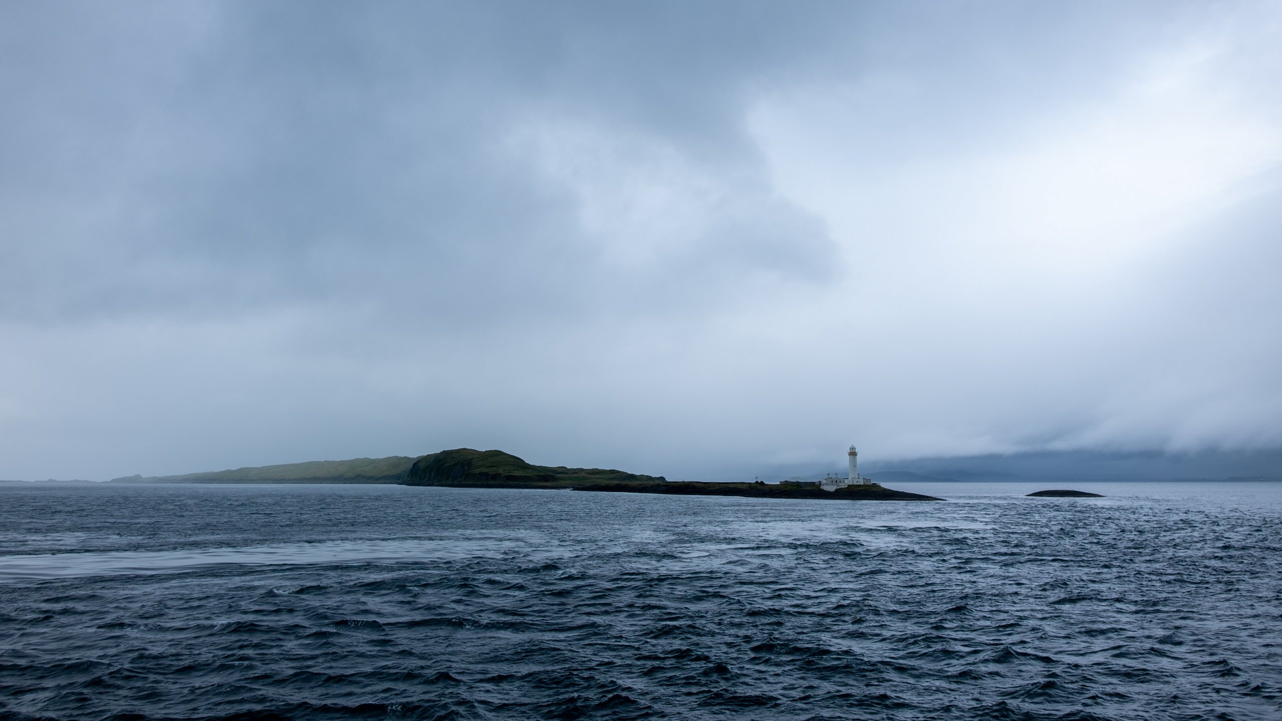 lighthouse and small island in distance on grey, overcast day with choppy seas