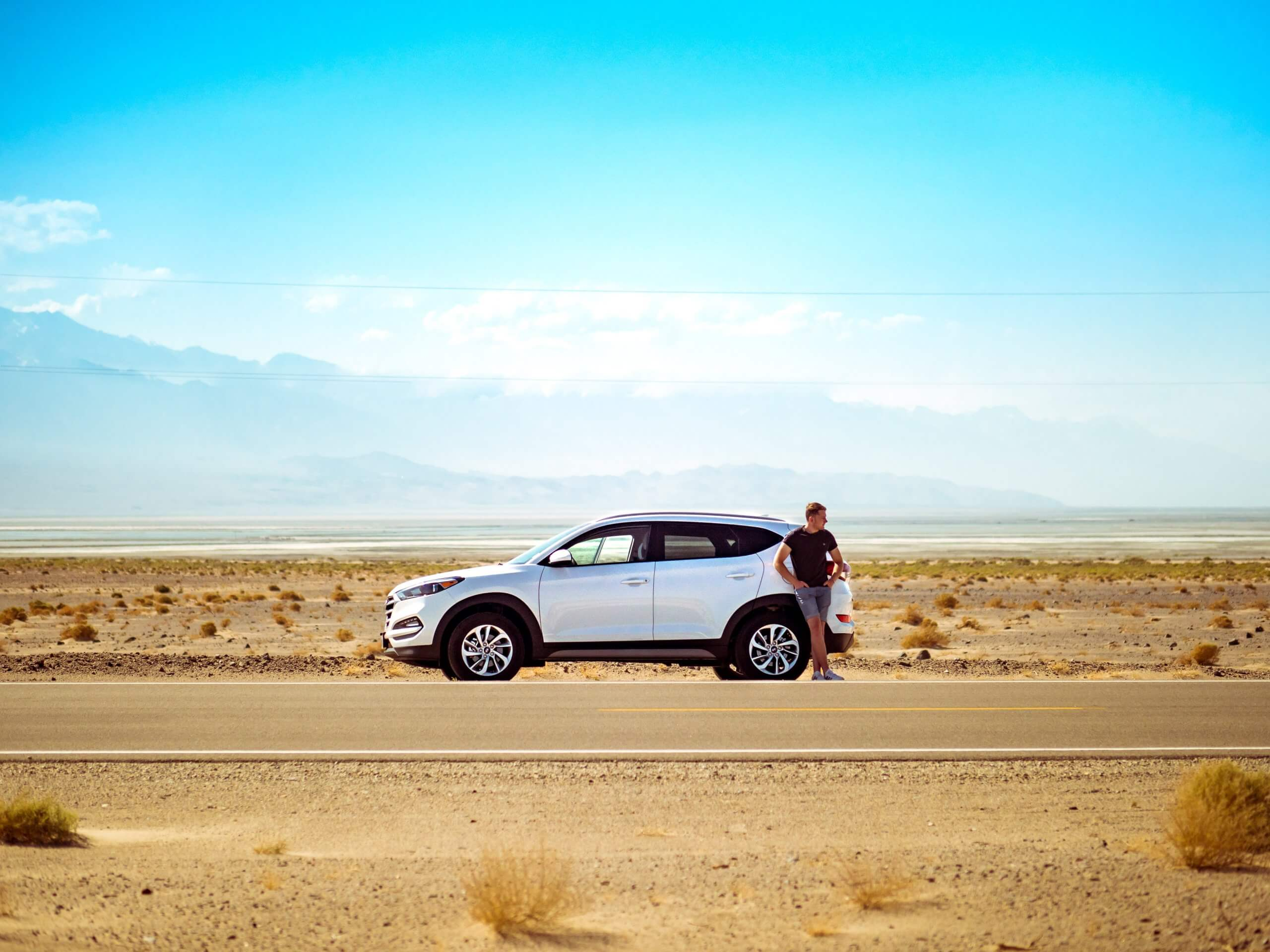 man stood by broken down car on desert road on beautiful day