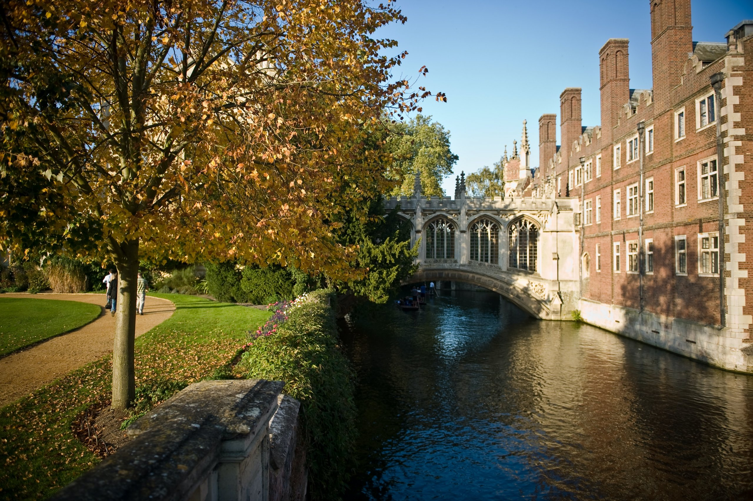 covered stone bridge across River with stone buildings on the right and green park on the left, Cambridge, UK