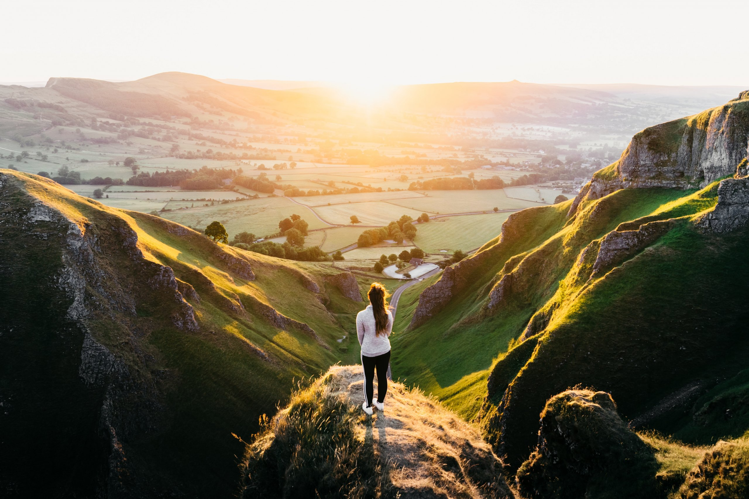 woman standing on rock overlooking green English valley at sunset