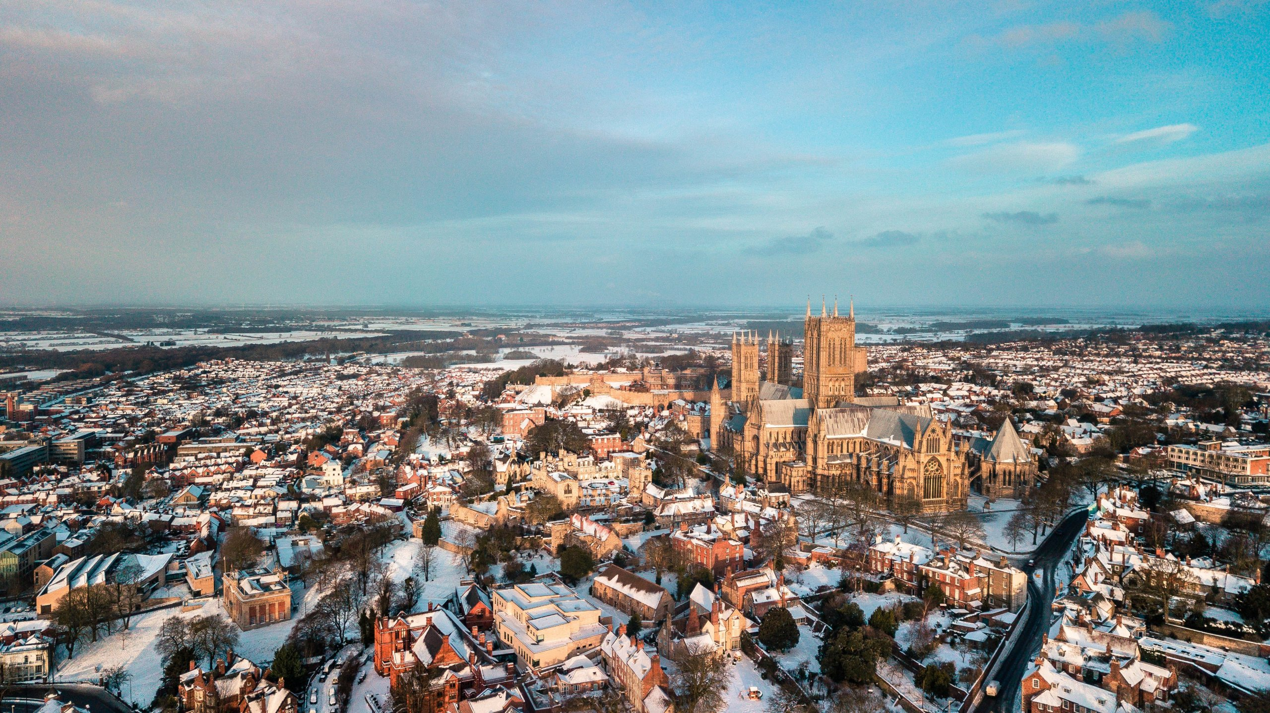 Lincoln city centre with Cathedral as focus on clear sunny day with snow covering the ground and house tops