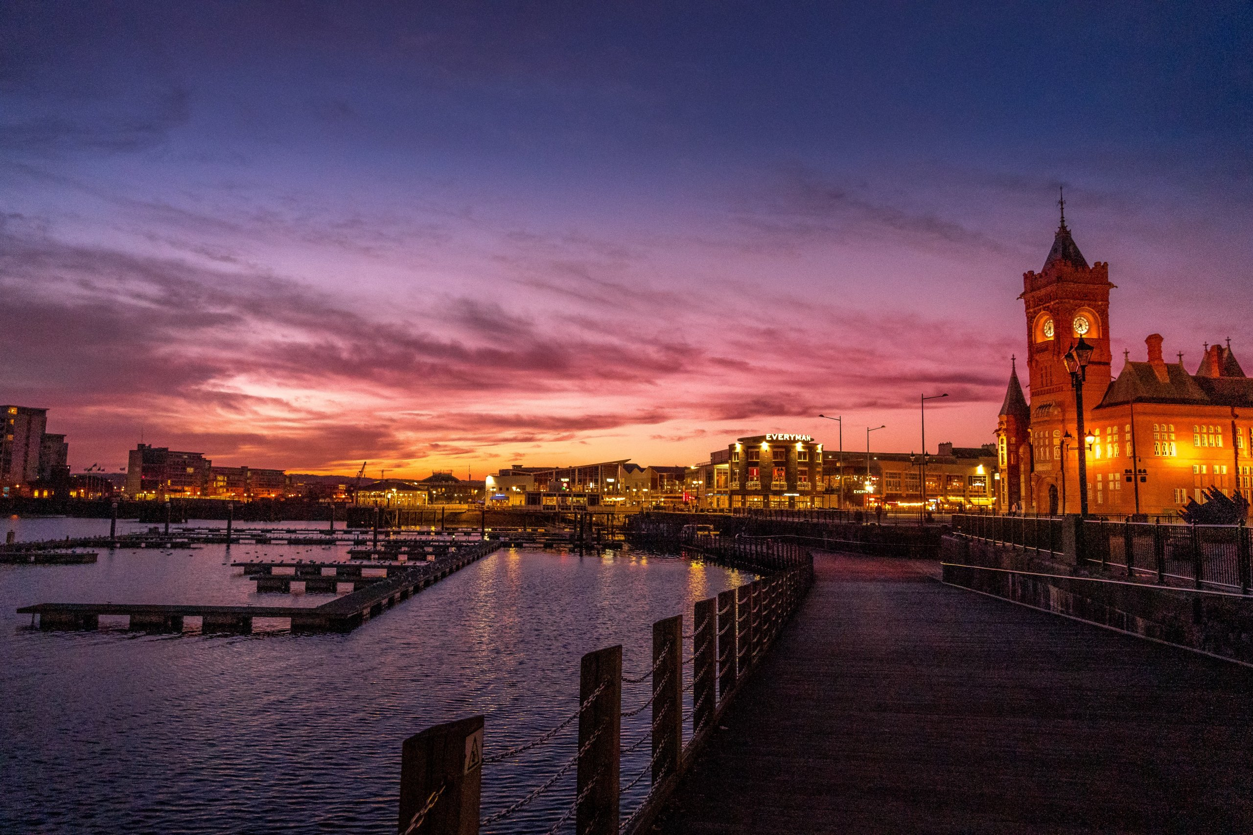 Sunset over Cardiff Bay, waterside marina with buildings and large clock tower lit up in early Welsh evening