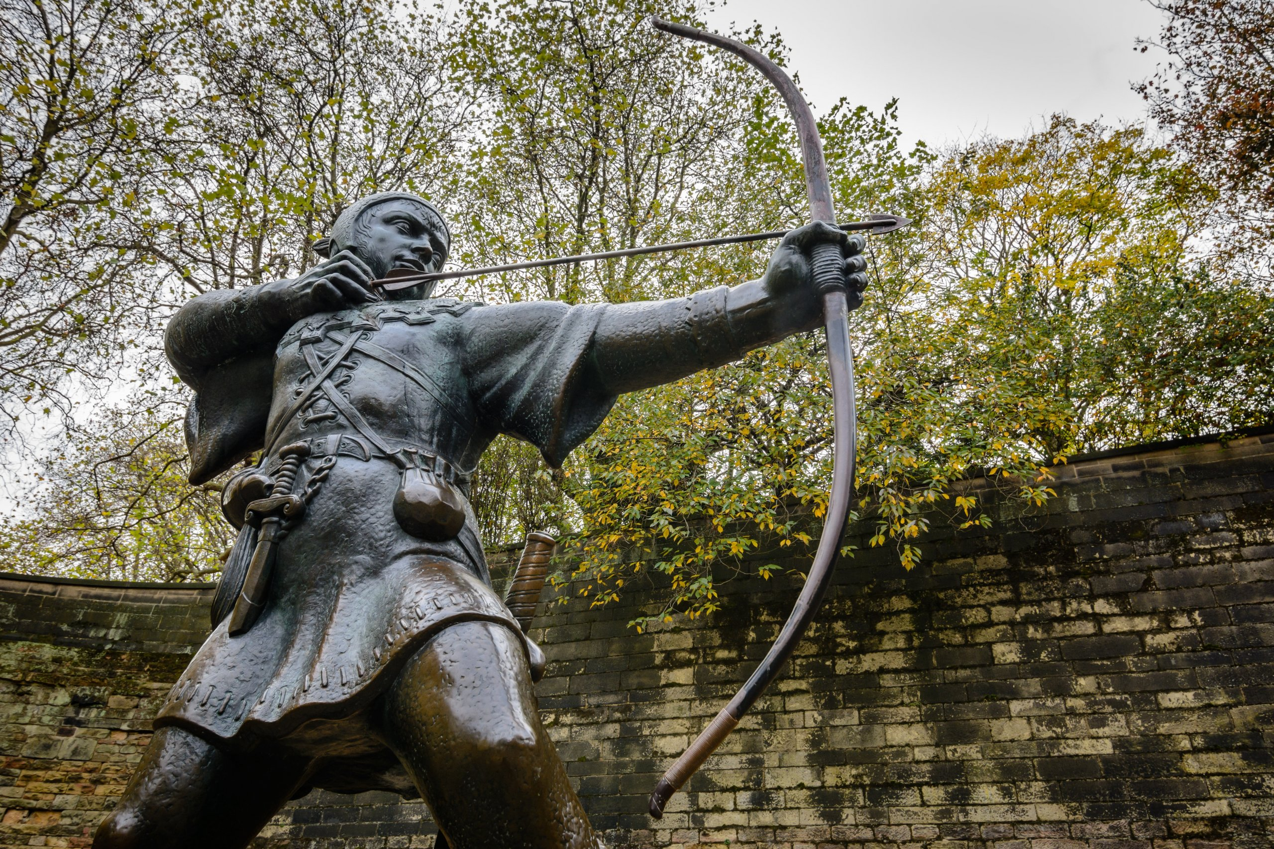 metal statue of man holding bow and arrow with stone wall and green trees in background