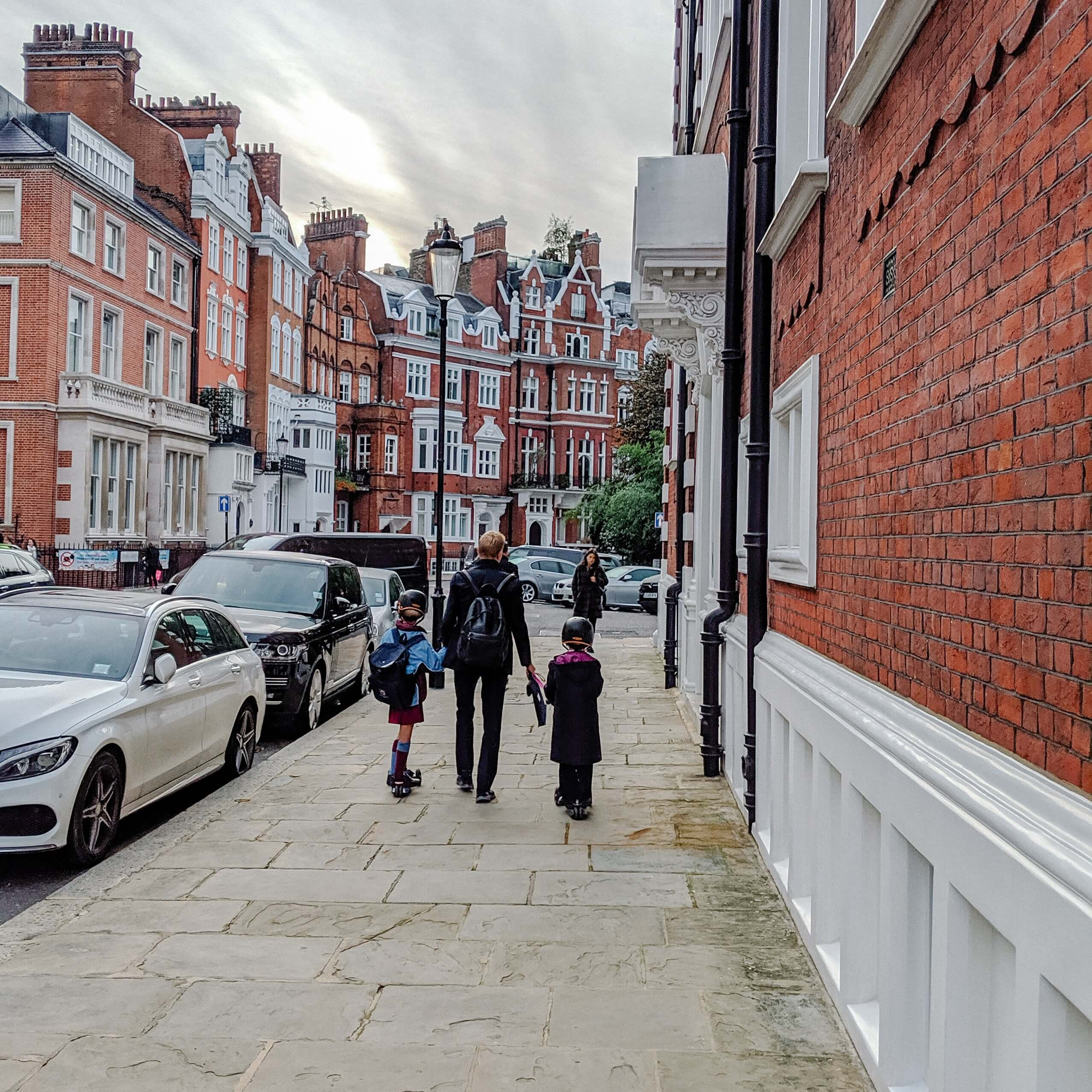 father with two children walking along UK pavement with cars parked on the road and female pedestrian walking towards them