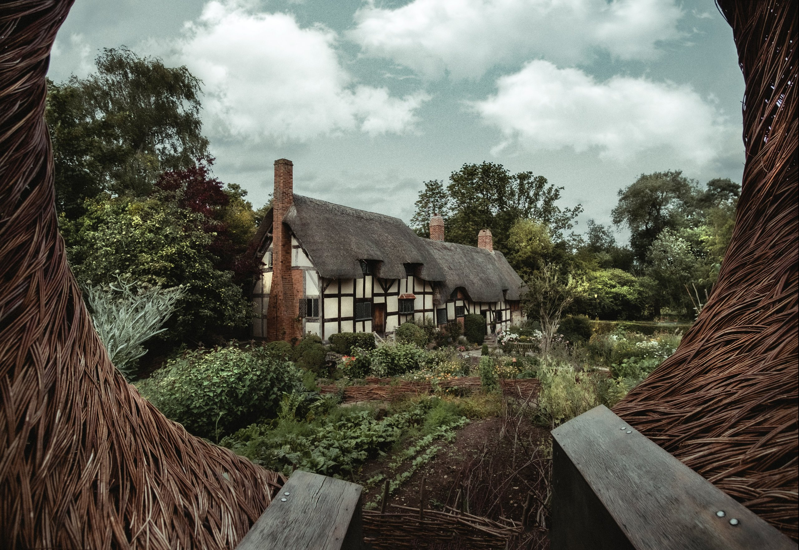Tudor farmhouse on cloudy day with large garden and trees in front