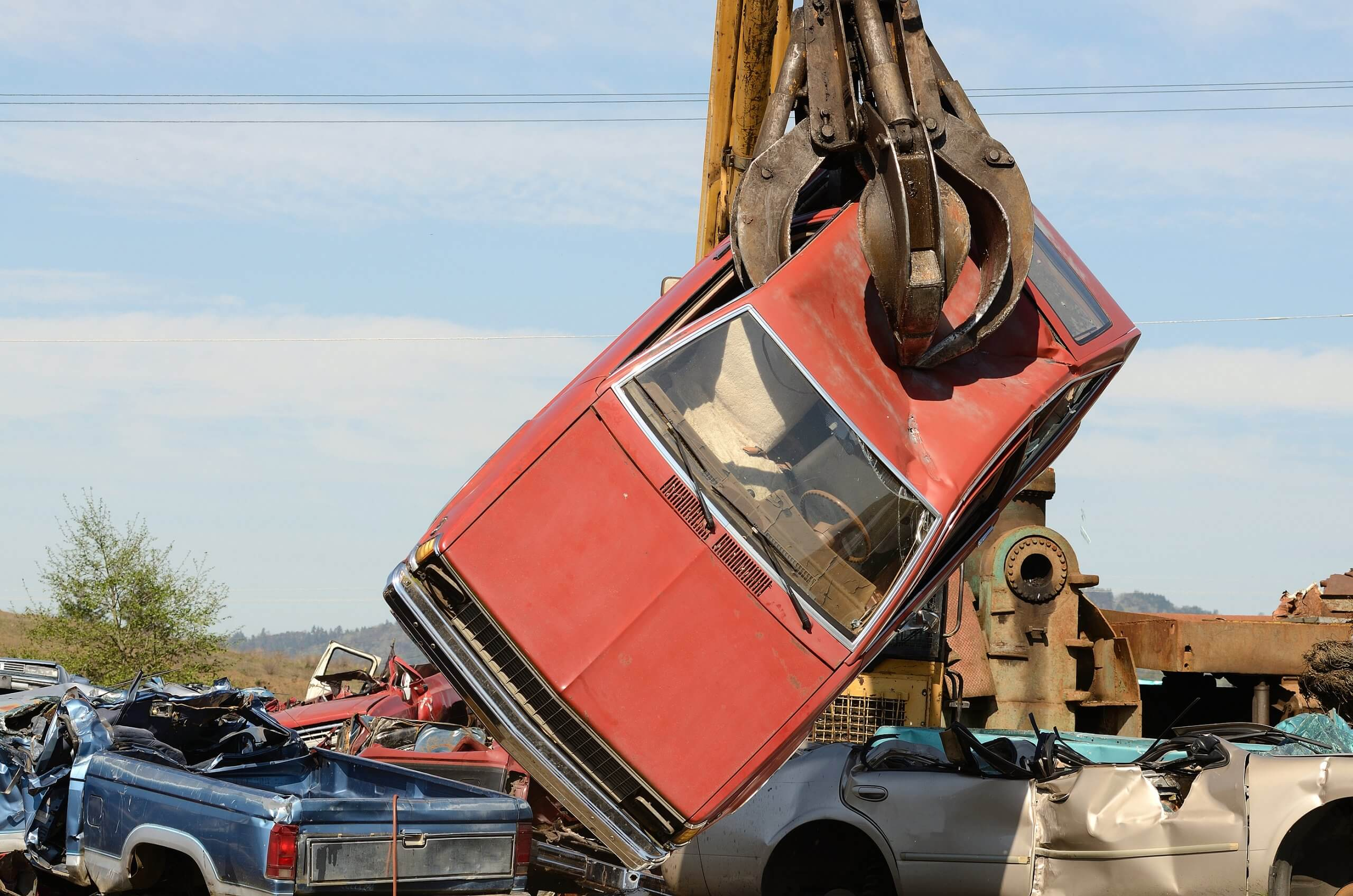 red car held by scrapping crane getting crushed in scrap yard