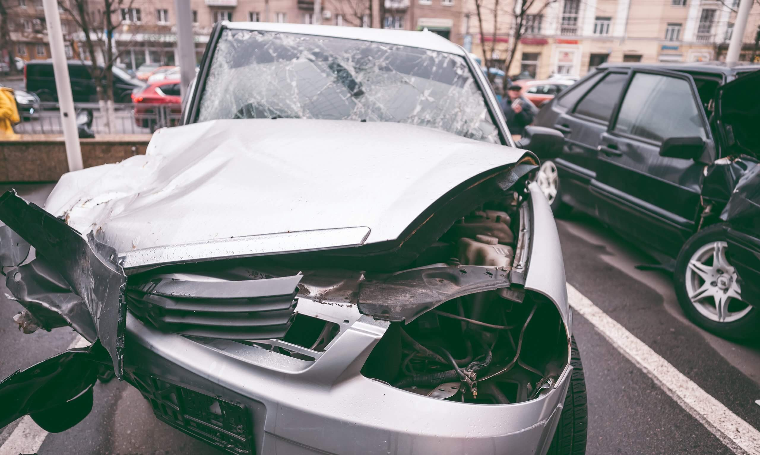 ruined silver car with crumpled bonnet and shattered windscreen as a result of car accident