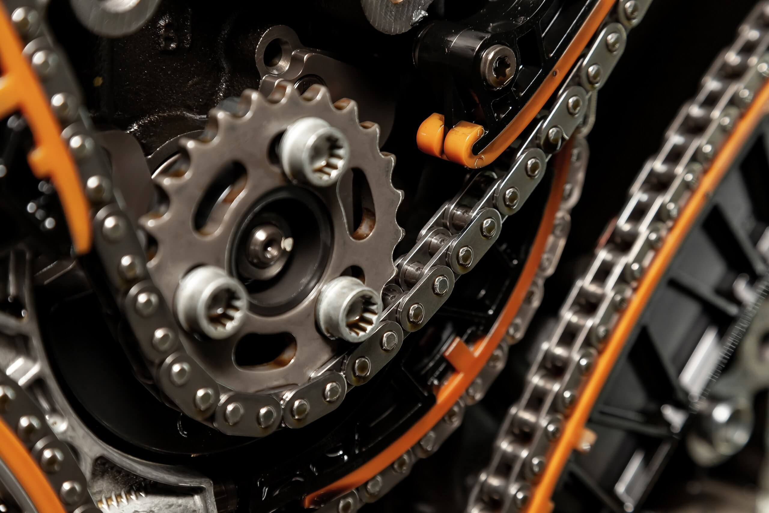 close up image of timing chain, linked metal chain attached to car engine