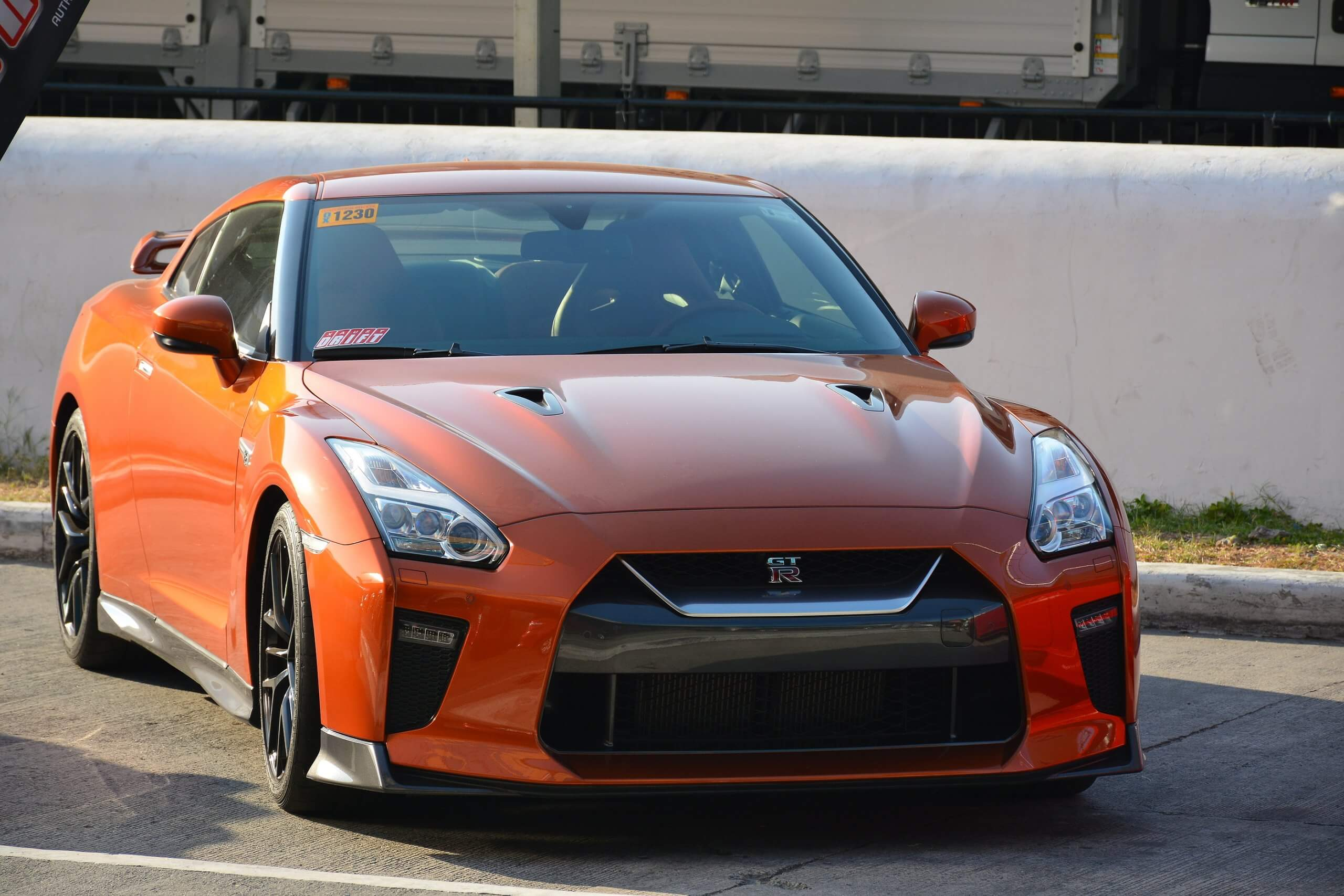 orange Nissan GTR parked in a car park on sunny day