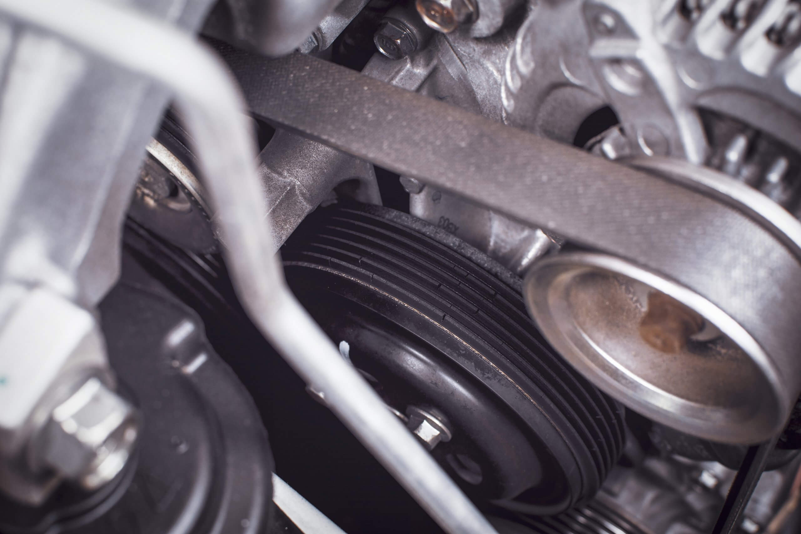 close up of glossy cambelt, shiny rubber belt attached to engine in engine bay