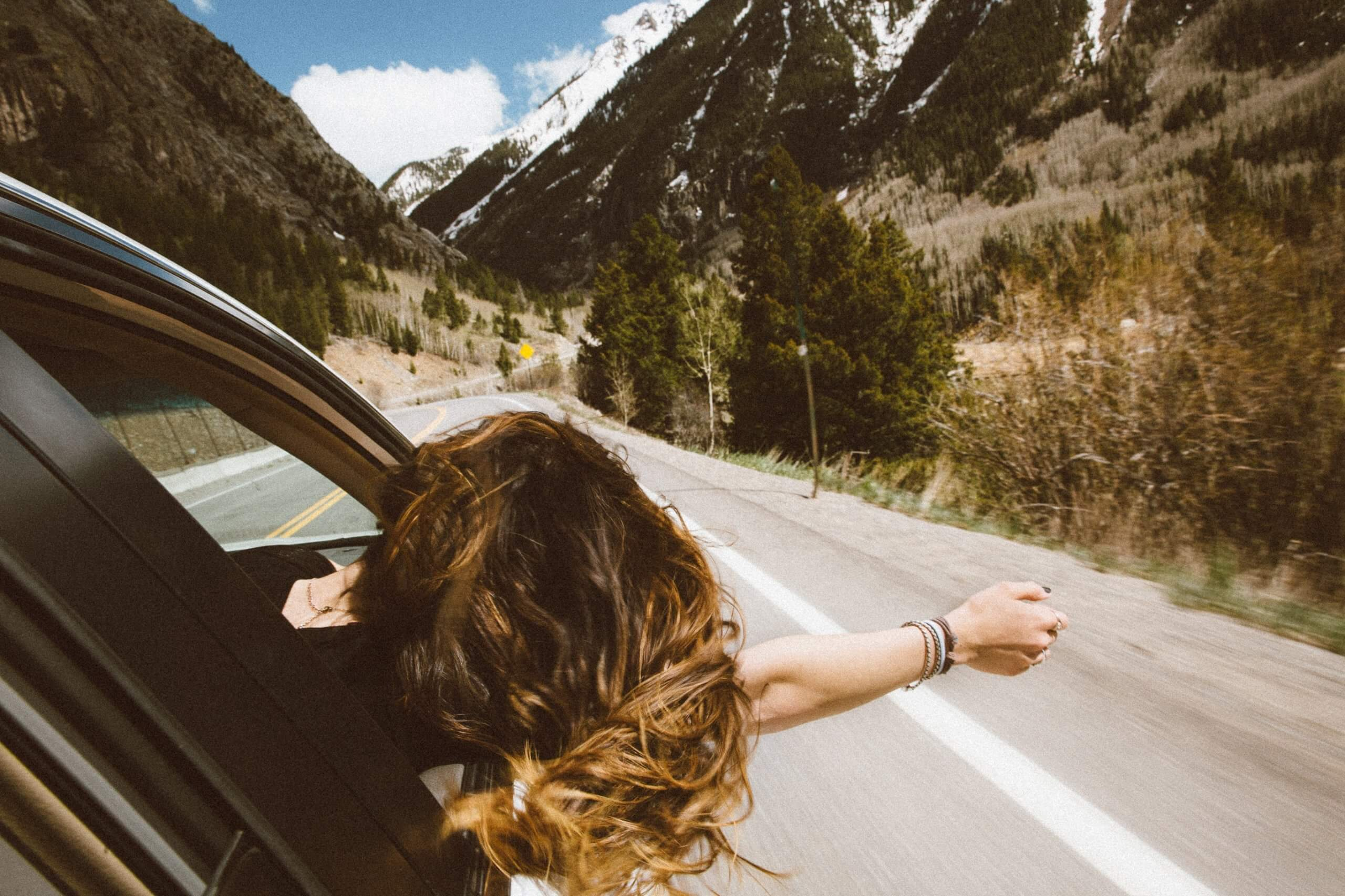 female passenger sticking her head out of car window on sunny day driving down mountain road