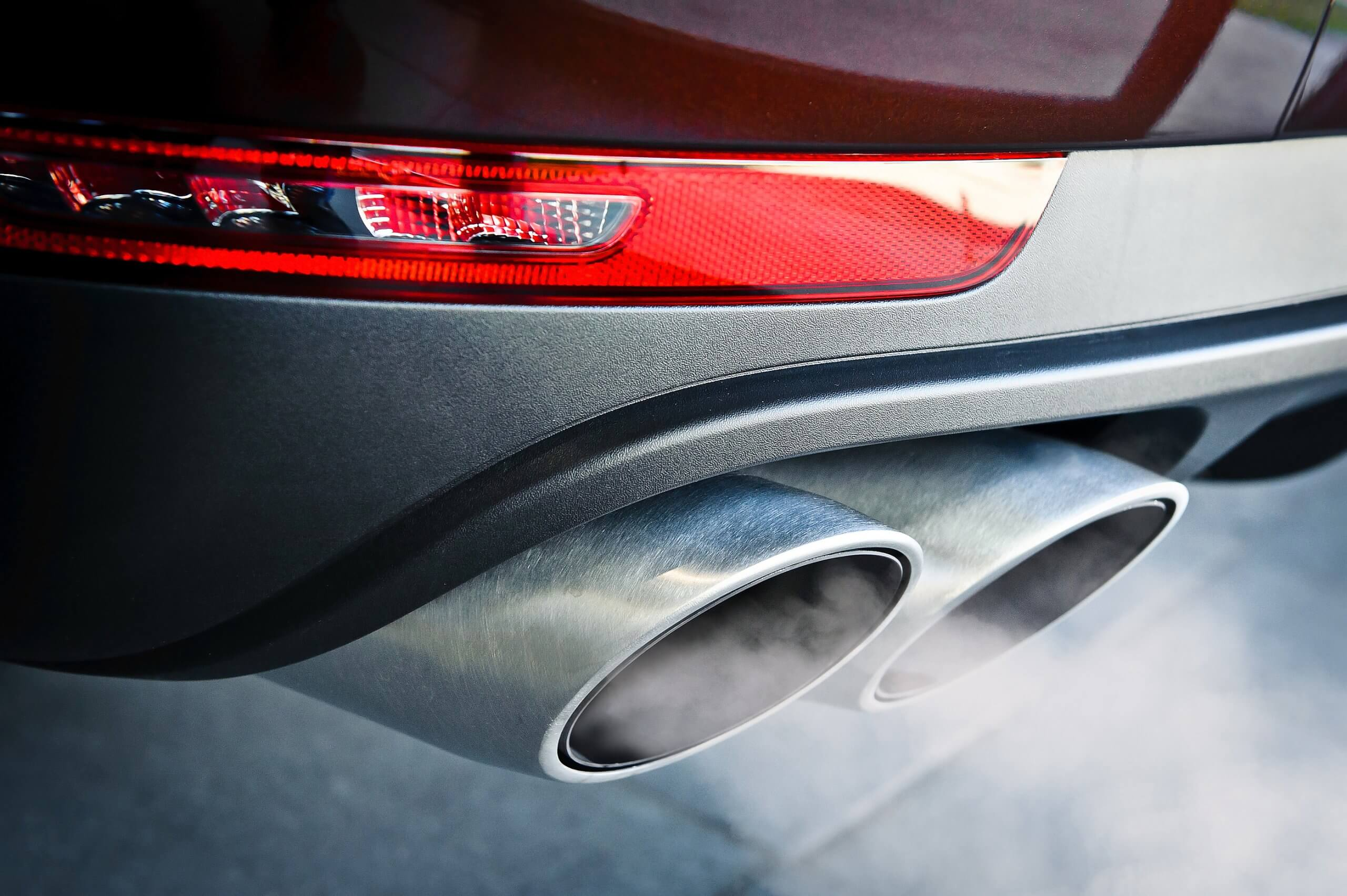 close up of dual car exhaust with faint exhaust gases