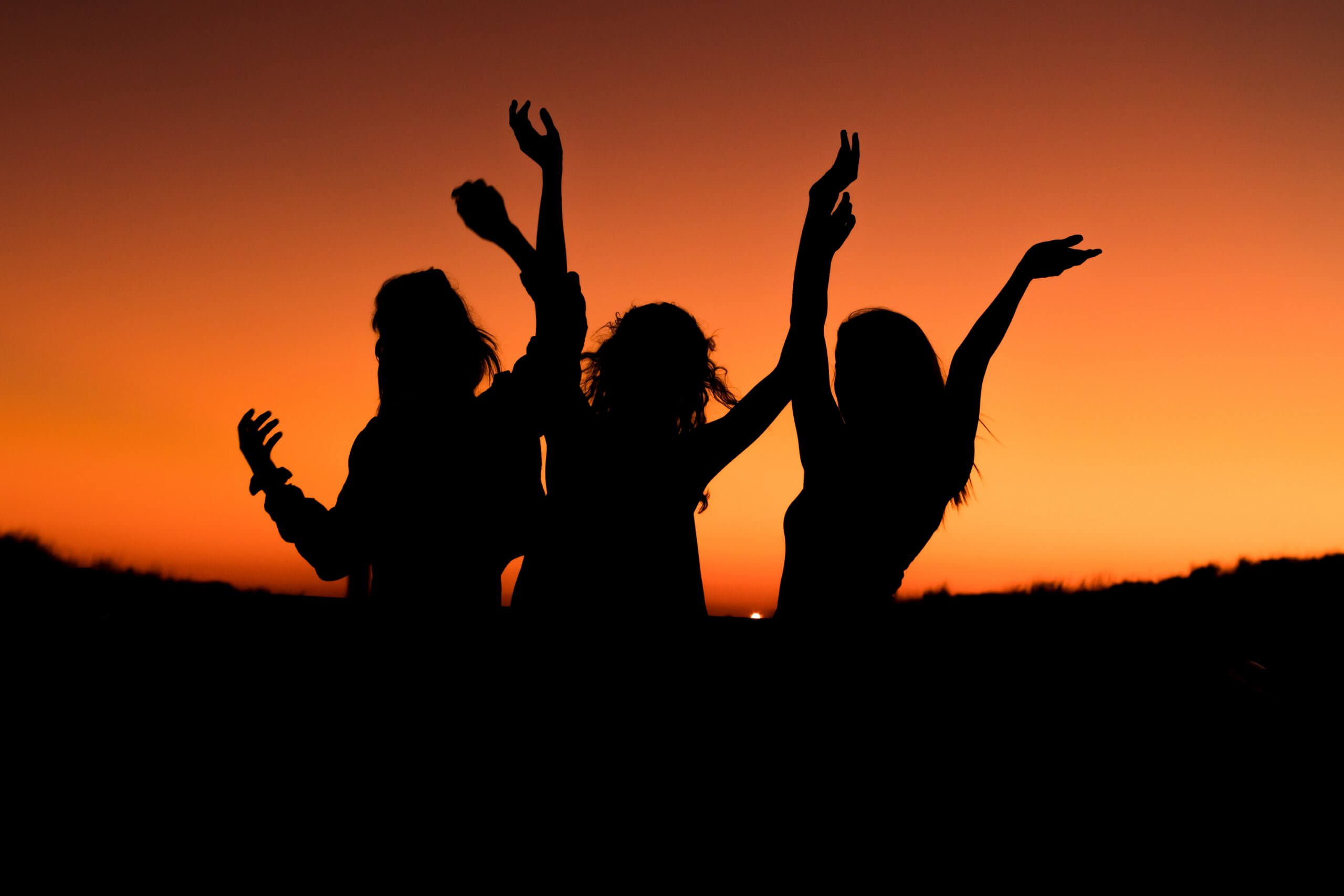 silhouettes of three women dancing at night with orange sunset sky in background