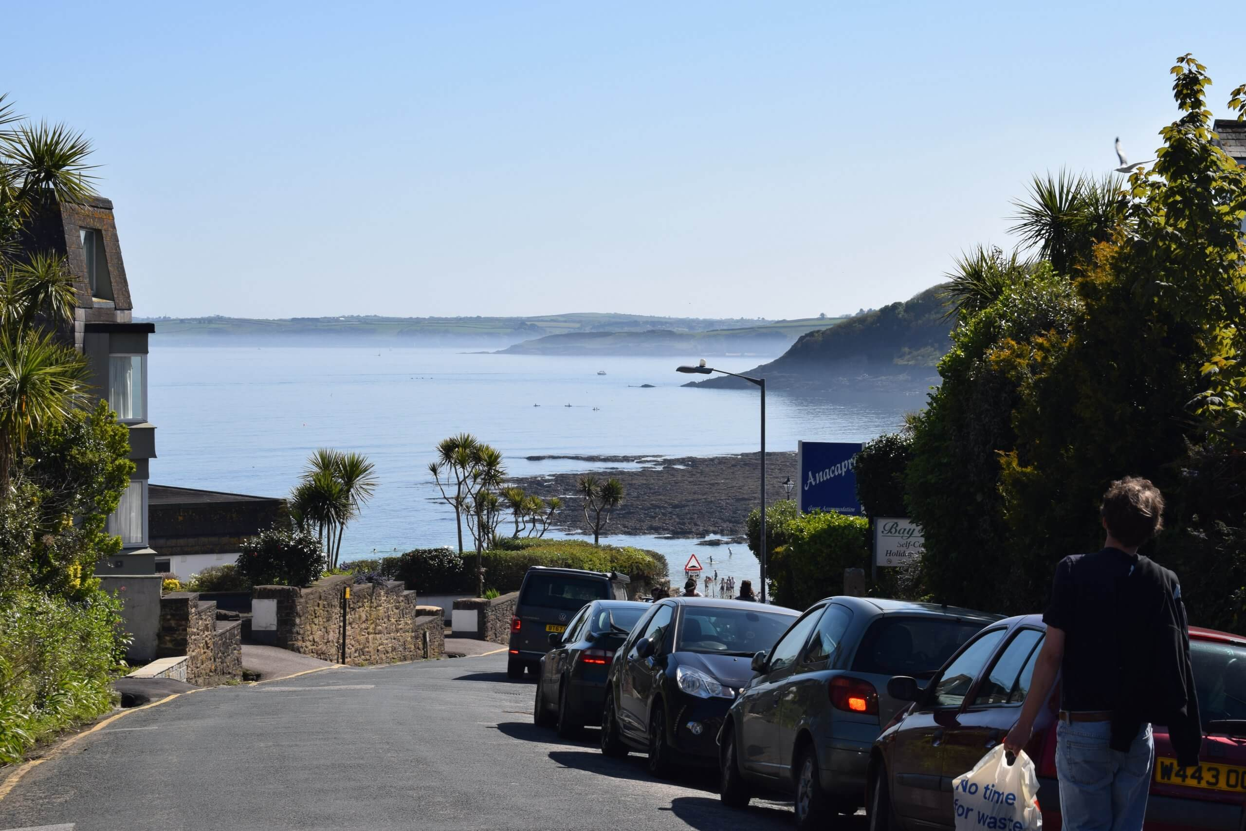 narrow UK street leading down hill to sea and clear blue sky, cars parked on right hand side of road