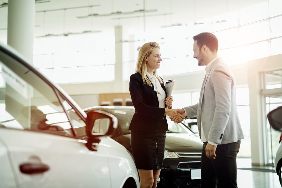 young saleswoman shaking hands with happy driver in auto workshop with white car in foreground and black car behind them