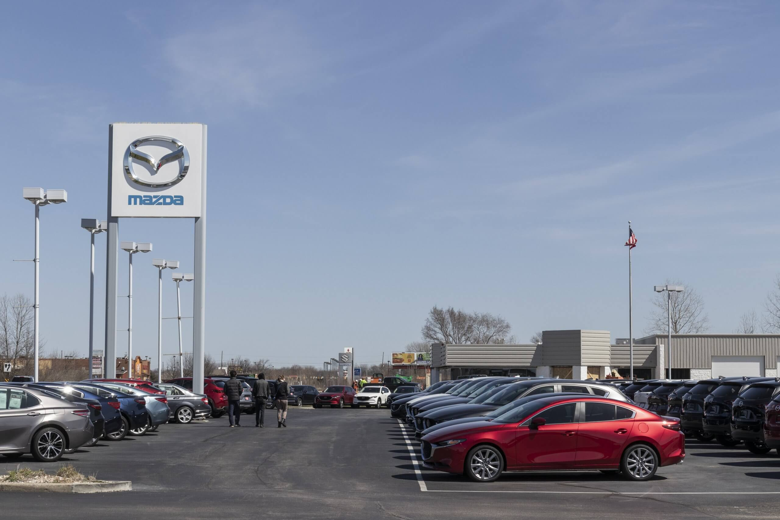 Mazda franchise dealership with rows of new Mazda cars parked in car park