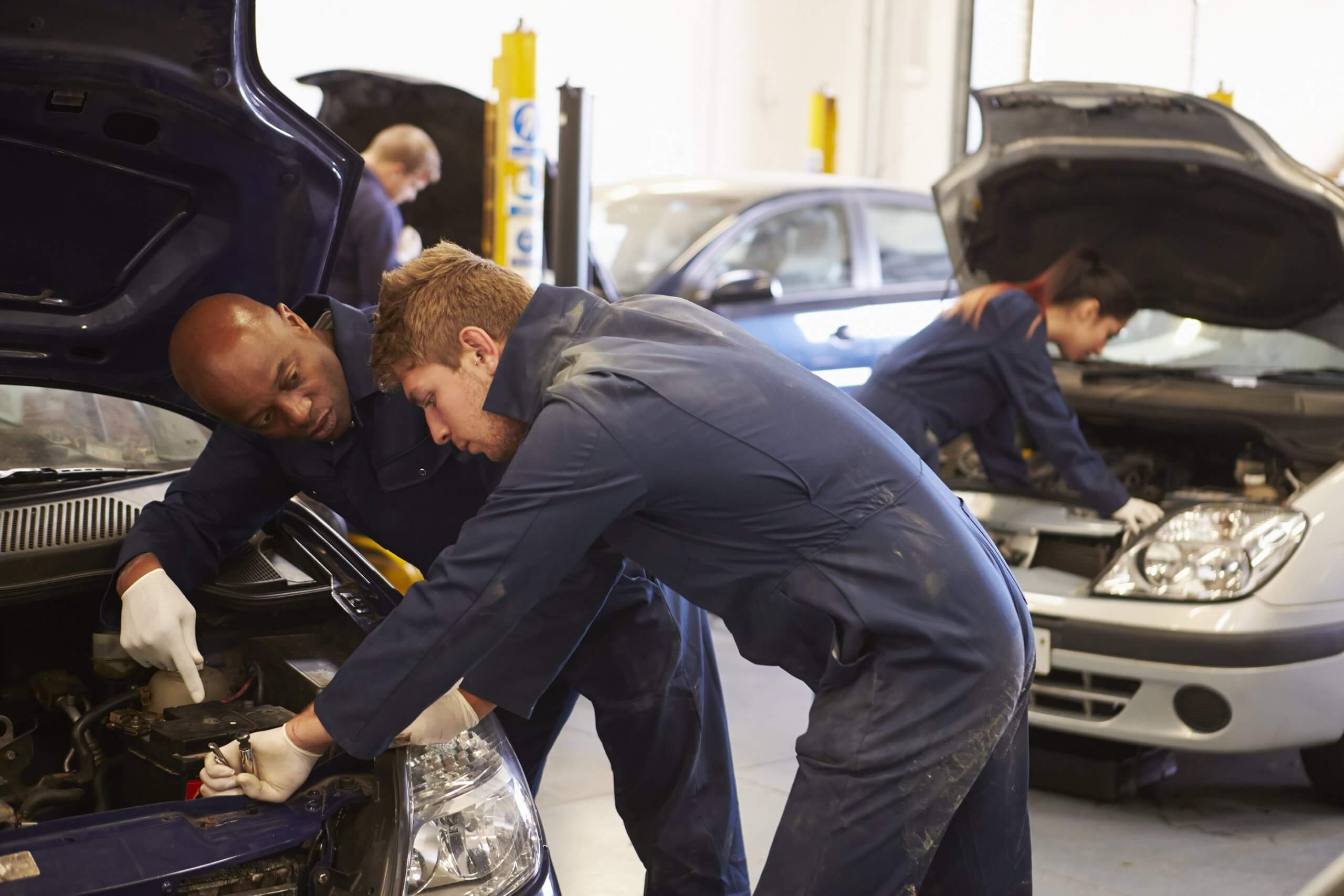 three mechanics working on separate cars in auto workshop, range of car services conducted simultaneously