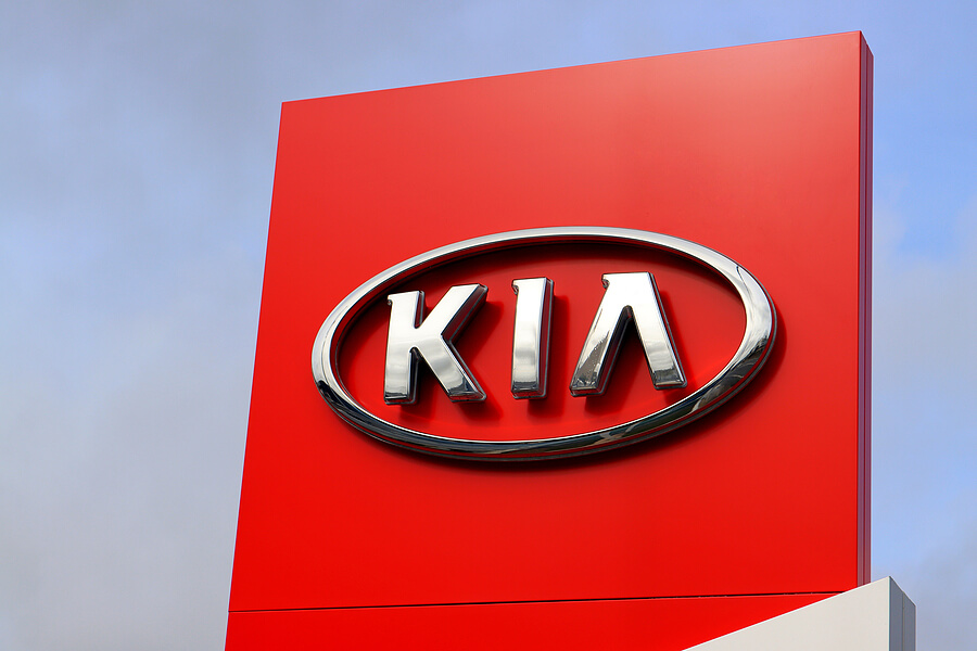 Kia logo on large red sign at one of their franchised dealerships